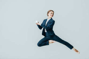 businesswoman in suit and ballet shoes jumping with cup of coffee, isolated on grey