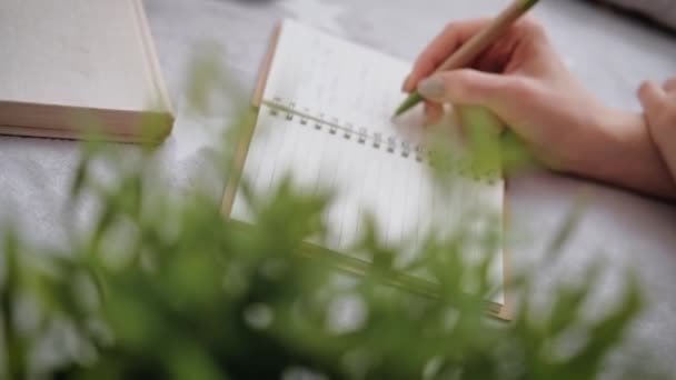 Young woman makes notes in her diary.