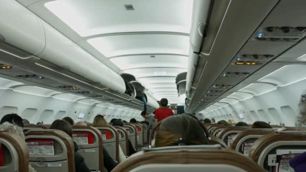 lidé si ukládají kufry na police na palubě letadla