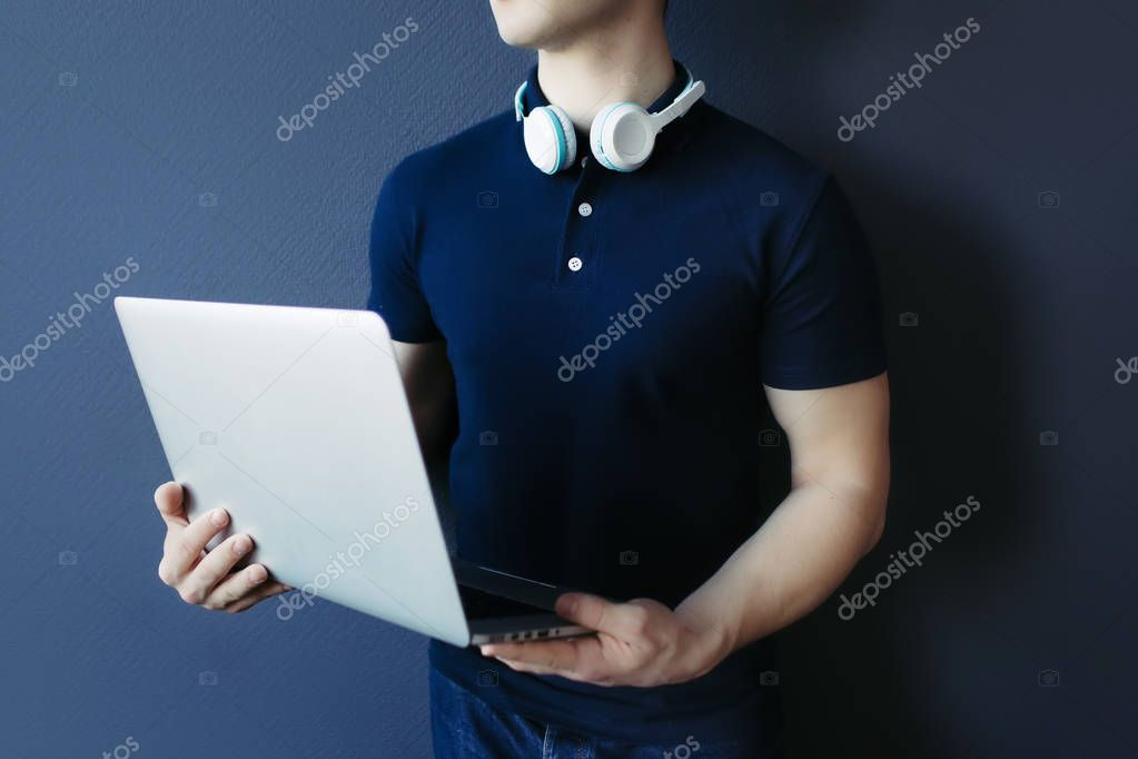 Young athletic man in t-shirt with headphones and laptop.