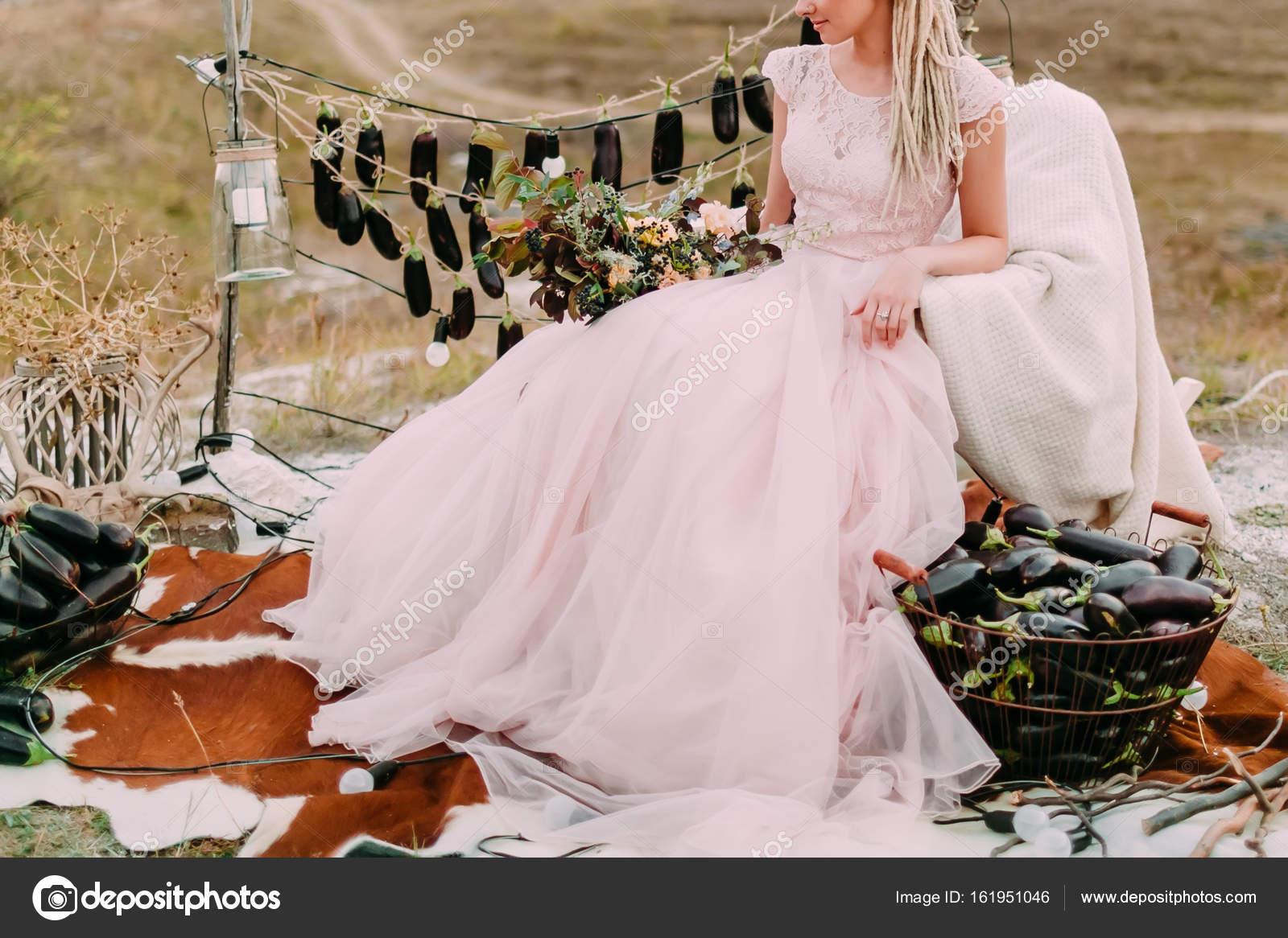 Rustikale Hochzeit im Wald, Braut sitzt in rosa Brautkleid in der ...