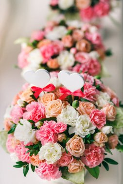 Flower arrangement of white and pink roses at the windowsill. Wedding ceremony