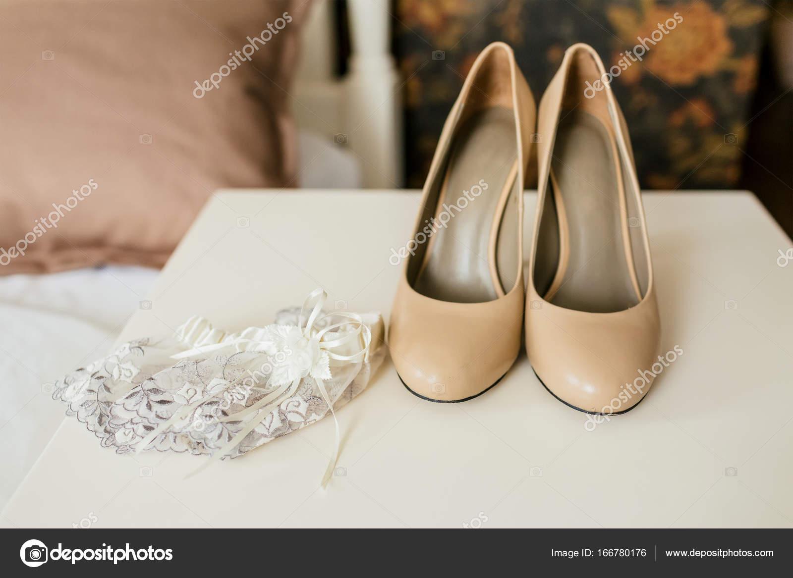 aca32258bdb3f4 Beige Schuhe auf einem Fersen und Spitzen-Strumpfband auf einem weißen  Tisch. Hochzeit Vorbereitung. Kunstwerk– Stockbild