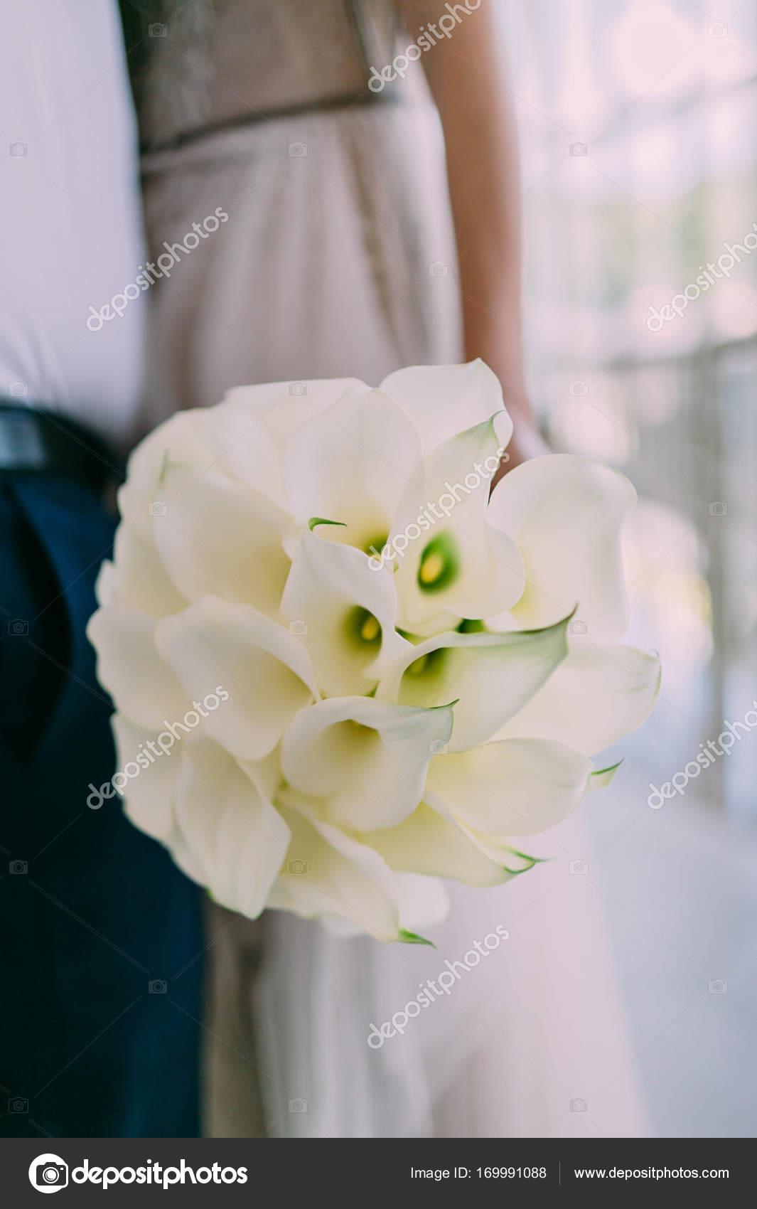 Beautiful wedding bouquet of calla flowers in hands of the bride beautiful wedding bouquet of calla flowers in hands of the bride artwork soft focus izmirmasajfo
