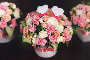 Flower arrangement of white and pink roses at the dark background. Wedding ceremony.
