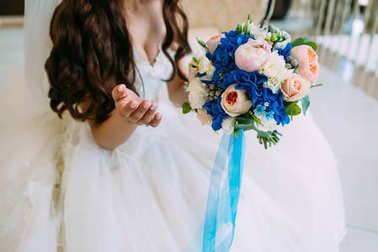 Blurred Bride holds bouquet with creamy roses and peonies and blue hydrangeas. Wedding morning. Close-up