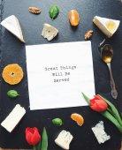 Fotografia Formaggi assortiti su un tavolo di pietra nero. Vista dallalto. Cucina gourmet. Cibo delizioso. Scheda con testo grandi cose saranno servite
