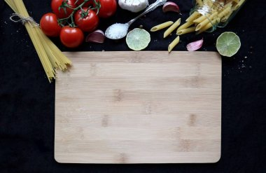 wooden cutting board and raw ingredients for cooking: pasta, cherry tomatoes, garlic, lime, salt. Food background with copy space. Flat lay