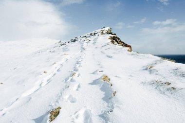 High steep snow-covered mountain peak near ocean and blue sky. Latrabjarg, Iceland
