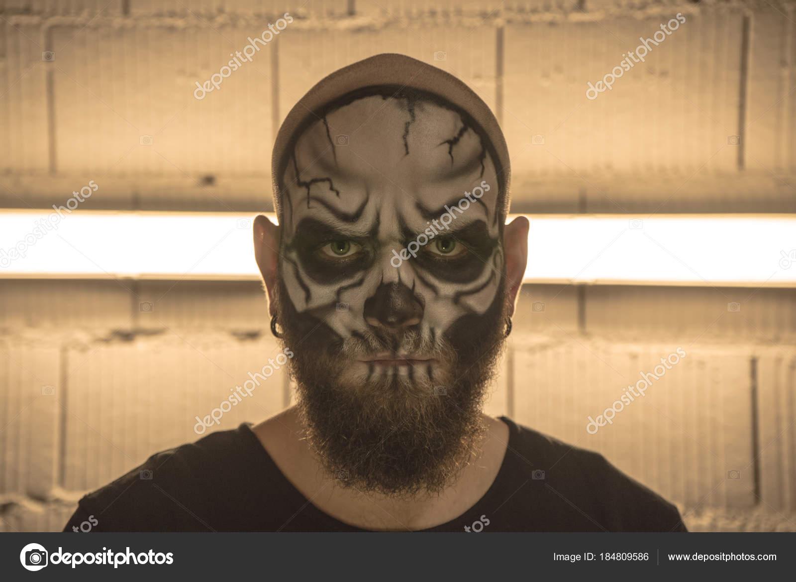Un tipo Calvo con una barba con un cráneo de maquillaje. Un hombre con una  calavera de maquillaje. Un terrible retrato de un hombre. 1709260c731