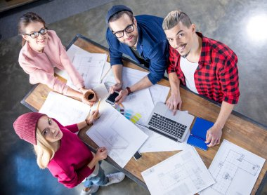 Group of male and female designers working at project with blueprints and smiling at camera stock vector