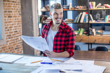 Portrait of smiling male architect holding blueprints and looking at distance stock vector