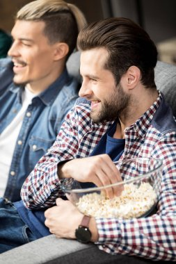 Smiling male friends sitting on couch and eating popcorn stock vector