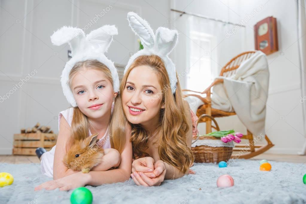 Mother and daughter playing with rabbit