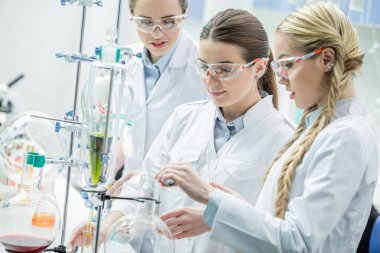Young female scientists in protective goggles making experiment in chemical laboratory stock vector