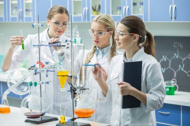 Young female scientists in lab coats making experiment in chemical laboratory stock vector