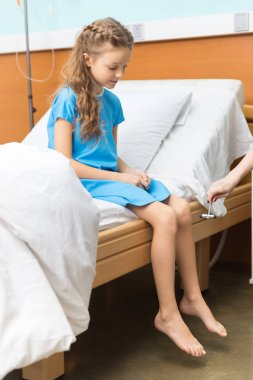 Little patient sitting on bed