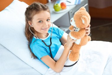 patient with stethoscope and teddy bear
