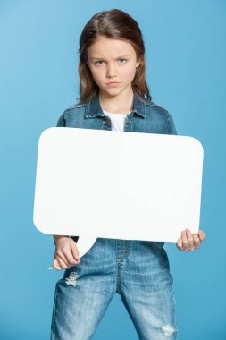 Upset little girl holding blank speech bubble and looking at camera isolated on blue stock vector