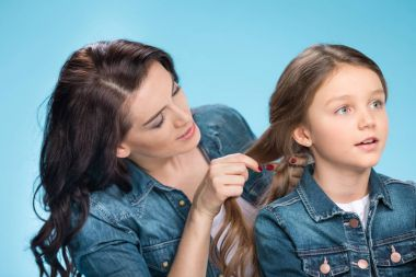 Mother and daughter braiding hair