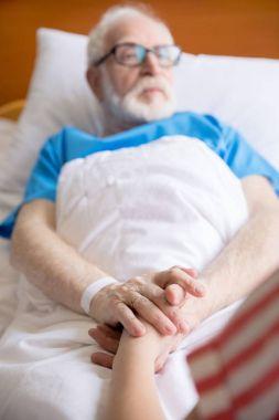 senior patient holding hands