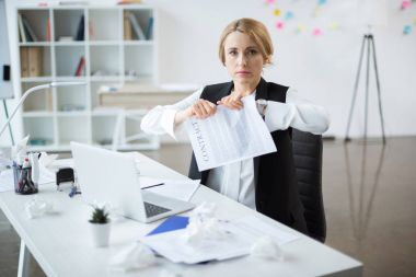 Serious blonde businesswoman tearing contract and looking at camera stock vector