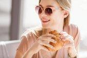 Fotografia Giovane donna mangia croissant