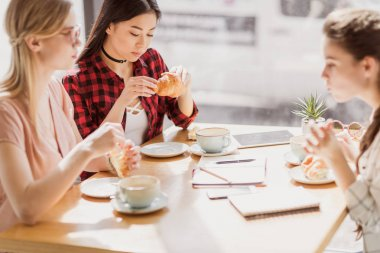 girls eating croissants and drinking coffee