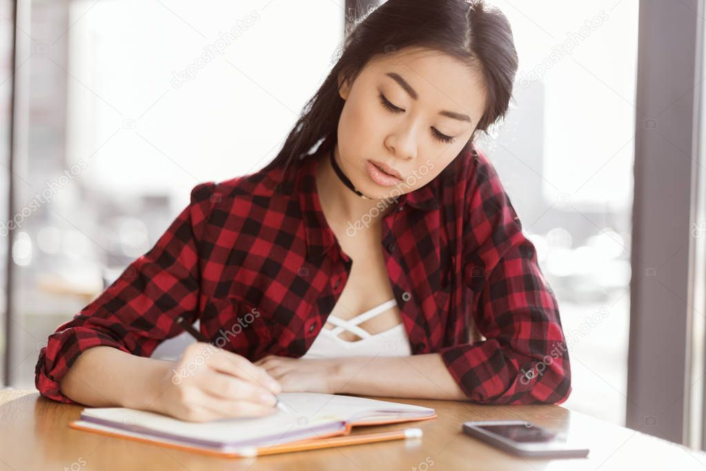 asian student studying in cafe