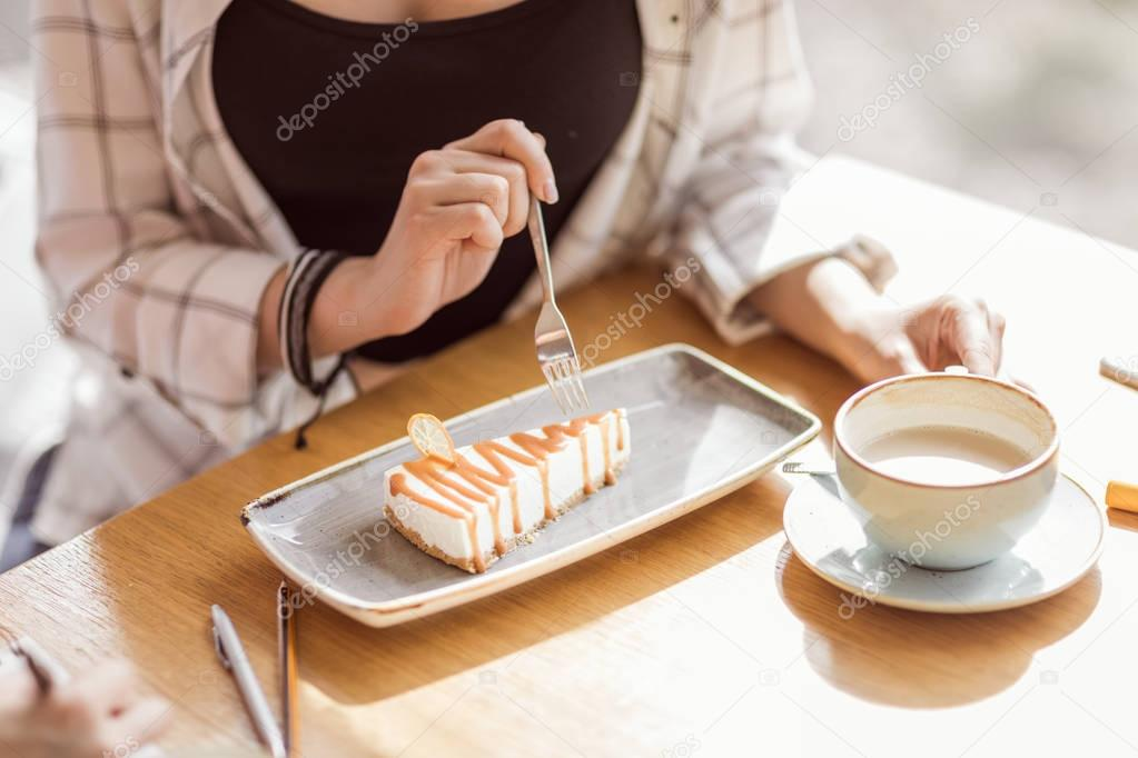 woman eating sweet dessert in cafe