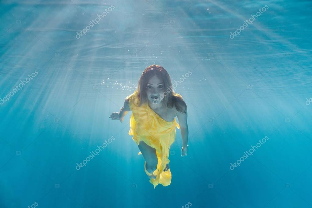 underwater picture of beautiful young woman in dress swimming in swimming pool
