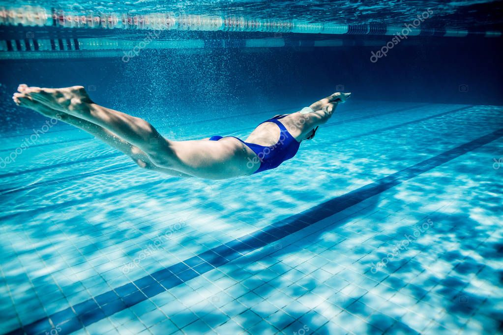 underwater picture of young female swimmer exercising in swimming pool