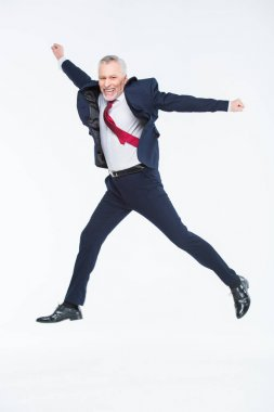 Mature businessman jumping