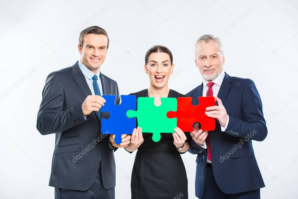 Businesspeople holding puzzle pieces