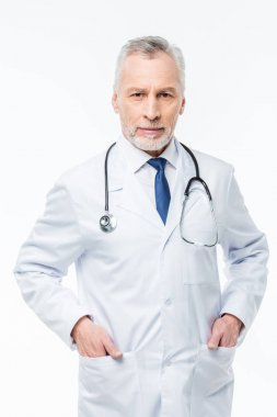 Mature male doctor with stethoscope and hands in pockets looking at camera isolated on white stock vector