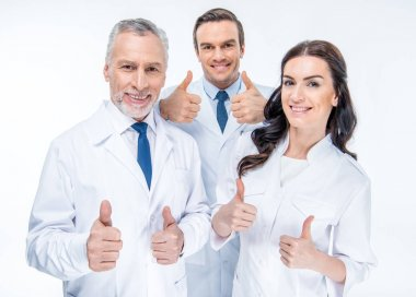 Portrait of three confident doctors smiling and showing thumbs up isolated on white stock vector