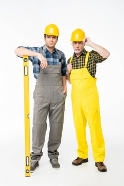 Two workmen in helmets standing with level tool and looking at camera  isolated on white stock vector