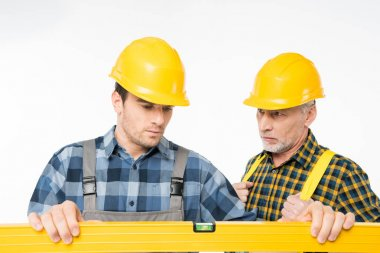 Two serious workmen working with level tool  isolated on white stock vector