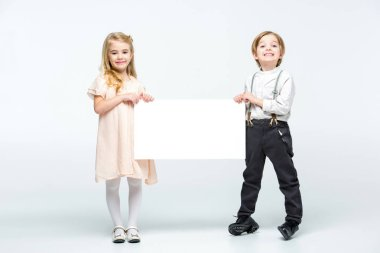 Happy little boy and girl holding blank card and looking at camera  isolated on white stock vector