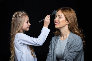 Girl doing makeup to her mother