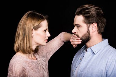 Woman covers mouth of man