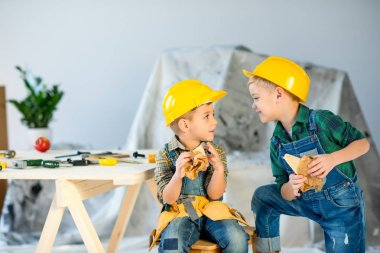 Two cute boys in helmets holding sandwiches and looking at each other stock vector