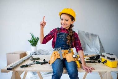 Little girl in tool belt and hard hat pointing up and smiling at camera in workshop stock vector