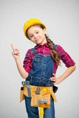 Little girl in tool belt and hard hat pointing up and smiling at camera on white stock vector