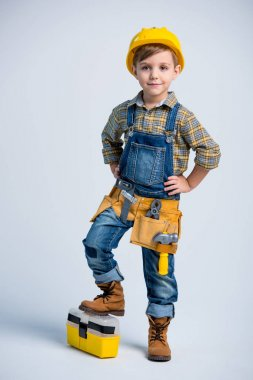 Cute little boy in yellow hard hat and tool belt smiling at camera on white stock vector