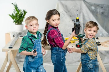 Two little boys and girl in workshop holding toy tools and looking at camera stock vector