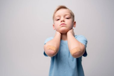 Little boy with patches on elbows