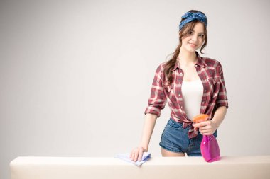 Young attractive woman holding spray bottle and rag and cleaning surface  isolated on grey stock vector