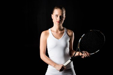 Serious young woman holding tennis racquet and looking at camera isolated on black stock vector