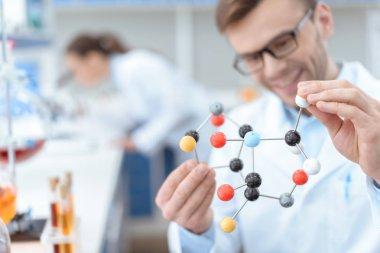 Smiling man scientist in eyeglasses holding molecular model in lab stock vector